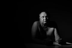 Sad senior man sitting with glasses over black. Dramatic black & white portrait of depressed old man sitting with glasses in hands Royalty Free Stock Photography
