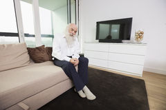 Sad senior man sitting on sofa in living room Royalty Free Stock Photography