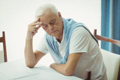 Sad senior man sitting at table Stock Photos