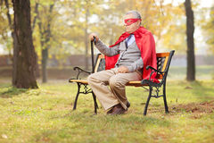 Sad senior in superhero outfit sitting in park Royalty Free Stock Images