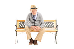 Sad senior thinking seated on a bench Stock Photo