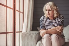 Sad senior woman. Beautiful sad senior woman is looking downward while sitting on couch at home royalty free stock image