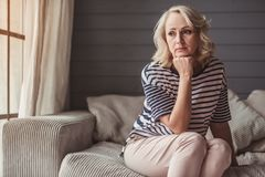 Sad senior woman stock images
