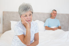 Sad senior woman on bed with husband in background Royalty Free Stock Image