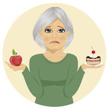 Sad senior woman choosing between chocolate layer cake and apple for dessert Stock Photos