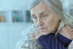 Sad  senior woman. Close up portrait of sad  senior woman sitting at table royalty free stock image