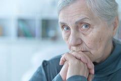 Sad  senior woman. Close up portrait of sad  senior woman sitting at table royalty free stock photos