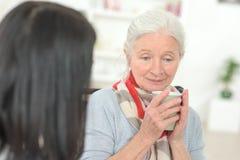 Sad senior woman drinking coffee stock image