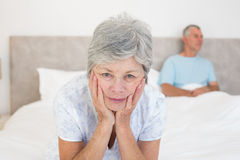 Sad senior woman with husband in bed Stock Image