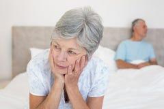 Sad senior woman with husband on bed Stock Photography