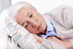 Sad senior woman lying on pillow at home. Age, sadness, trouble, problem and people concept - sad senior woman sleeping on pillow at home Royalty Free Stock Photos