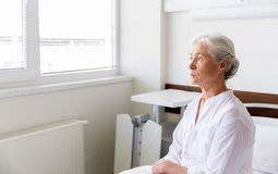 Sad senior woman sitting on bed at hospital ward stock photos
