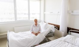 Sad senior woman sitting on bed at hospital ward. Medicine, healthcare and old people concept - sad senior woman sitting on bed at hospital ward Royalty Free Stock Image