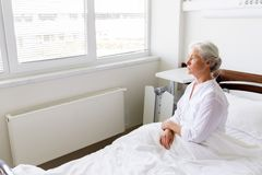 Sad senior woman sitting on bed at hospital ward stock images