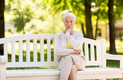Sad senior woman sitting on bench at summer park. Old age, retirement and people concept - sad senior woman sitting on bench at summer park Royalty Free Stock Photography