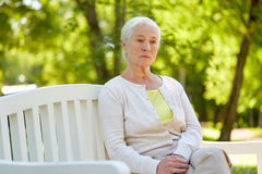 Sad senior woman sitting on bench at summer park royalty free stock images