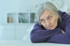 sad  senior woman sitting at table Royalty Free Stock Images
