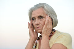 Sad  senior woman in summer field Stock Images