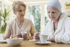 Sad senior woman and caregiver drinking tea. Sad senior women and caregiver drinking tea in the nursing house stock images