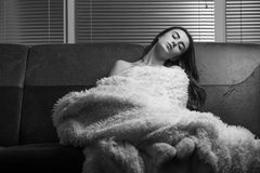 Sad sensual girl. In fur sitting on sofa, monochrome Stock Photos