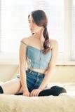 Sad sensual girl. Sitting in sun rays, toned image Stock Photos