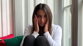 Sad sepressed young woman crying sitting on a window at home stock video