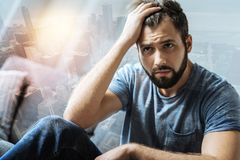 Sad serious man sitting and looking aside. Im alone. Sad serious unshaken man sitting in the bright room holding hand near head and looking aside Stock Photo