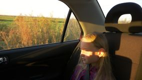 Sad serious young girl traveling by car summer evening. Rural scene at window. Girl close up handheld shot. Sad serious young girl traveling by car summer stock footage