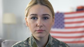 Sad servicewoman looking camera with american flag on background, memorial day. Stock footage stock footage