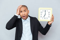 Sad shocked african man holding big clock Stock Photo
