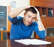 Sad shocked guy looking at document at home Royalty Free Stock Images