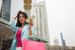 Sad shopaholic girl look at one dollar. Sad shopaholic Asian girl look at One Dollar bill in hand with headache sign in modern city. No more money to shopping in stock image