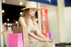Sad shopping woman spend all money. Sad young pretty woman sitting in shopping mall with shopping bag around thinking. She is holding credit cards looking upset Stock Photos