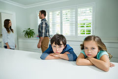 Sad siblings listening their parents having an argument at home Stock Images
