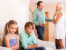 Sad siblings and quarrel parents Stock Photos