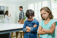 Sad siblings standing with arms crossed while parents arguing in background Stock Images
