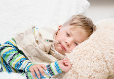 Sad sick boy with thermometer laying in bed Stock Images