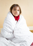 Sad sick girl covering with white blanket Royalty Free Stock Image