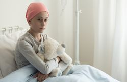 Sad sick girl with pink headscarf hugging plush toy in the hospital stock images