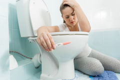 Sad sick woman sitting in bathroom and holding positive pregnanc Stock Photos