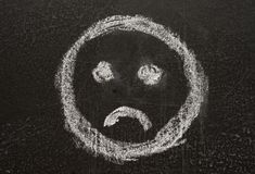Sad. Sign smiley, sketched with white chalk on the blackboard Stock Image