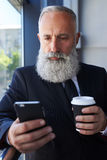 Sad sir age of 50-60 holding cup of coffee and surfing in phone Stock Photo