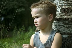 Sad six year old. Six year old sitting against a tree being sad and thinking stock photo