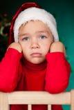 Sad small boy in santa hat Stock Image