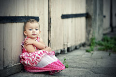 Sad small girl. Sitting in front of the garage Stock Image