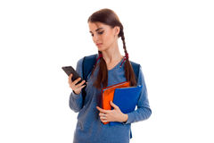 Sad smart student girl with backpack on her shoulders and folder for notebooks in her hands looking at mobile phone Royalty Free Stock Photos
