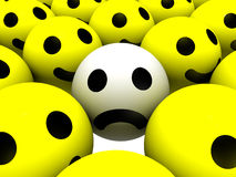 Sad Smiley. Smiley with sad face surrounded by ones with happy faces Stock Images