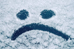 Sad smiley emoticon face drawn on snow covered glass Stock Photos