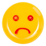 Sad smiley face made on plate Stock Photography