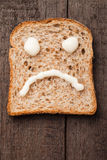 Sad smiley. Made from mayonnaise on slice of bread Royalty Free Stock Images